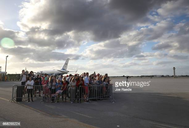 People watch as US President Donald Trump arrives on Air Force One at the Palm Beach International Airport to spend Easter weekend at MaraLago resort...