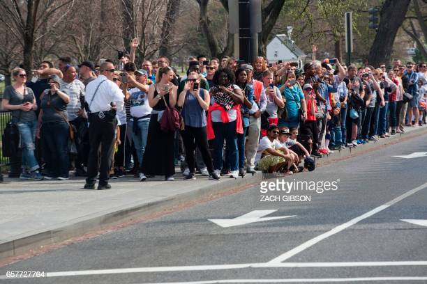 People watch as US President Donald Trump's motorcade pulls into The White House on March 25 2017 in Washington DC / AFP PHOTO / ZACH GIBSON