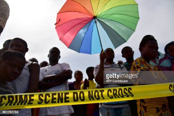 People watch behind a police tape on the beach of PortBouet in Abidjan near the wreckage of a cargo plane that crashed off Ivory Coast killing four...