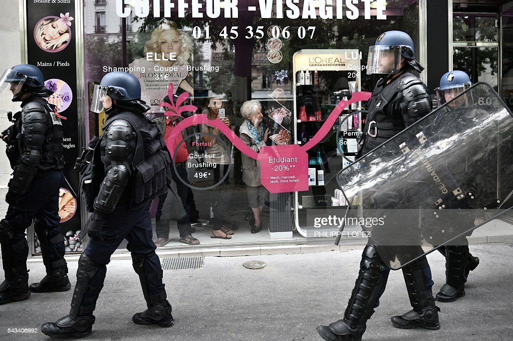 People watch behind a shop window French anti-riot police patroling during a demonstration against controversial labour reforms, on June 28, 2016 in Paris. Unions have called repeated strikes and marches in opposition to the law, which seeks to bring down France's intractable 10-percent unemployment rate by making it easier to hire and fire workers. / AFP / PHILIPPE