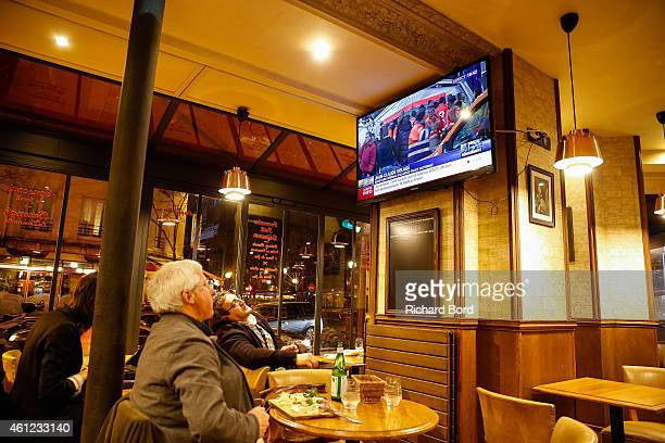 People watch breaking news on the television in a cafe as police mobilize to a hostage situation at Porte de Vincennes on January 9 2015 in Paris...