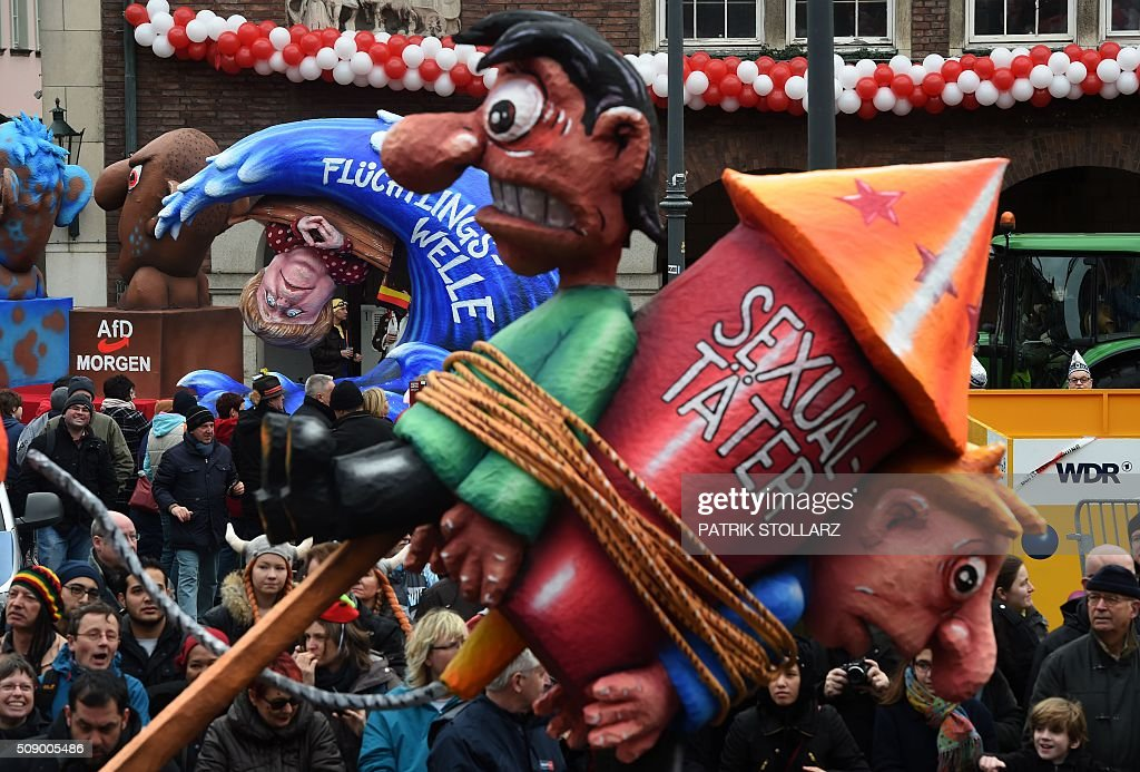People watch carnival floats parked in front of the city hall in Duesseldorf, western Germany, after the Rose Monday (Rosenmontag) street parade has been cancelled on February 8, 2016. Traditional Rose Monday carnival parades in several western German cities have been cancelled due to stormy weather. / AFP / PATRIK STOLLARZ