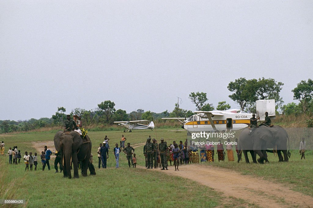 People watch elephant trainers ride African elephants near two small aircraft in Virunga National Park. The animals are part of a training experiment in the park.