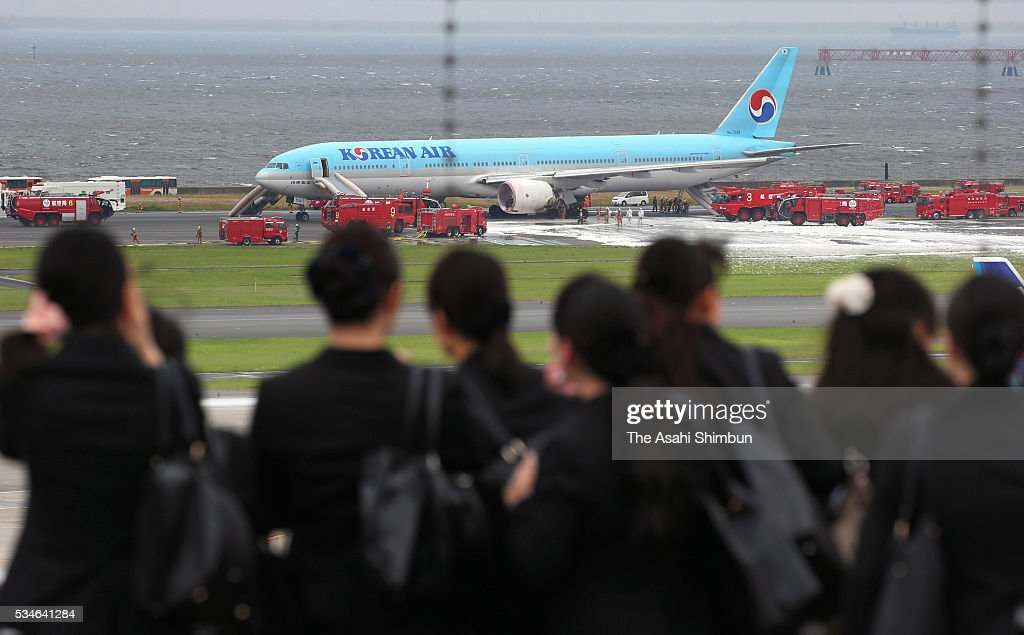 People watch fire fighters battling with fire at an engine on the left side of the Korean Air 2708 bound for Seoul at the Haneda International Airport on May 27, 2016 in Tokyo, Japan. 319 passengers and crews have safely evacuated. C runway has been closed.