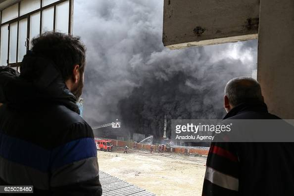 People watch firefighters as they try to extinguish fire at 3storey office in Istanbul's Bayrampasa Turkey on November 22 2016