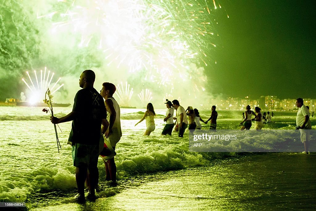 People watch fireworks along Copacabana Beach in Rio de Janeiro on January 1, 2013, during celebrations by over three million people attending New Year's Eve festivities. World cities from Sydney and Hong Kong to Dubai and London rang in the New Year with spectacular fireworks, as revelers at Times Square in New York sought to top off the global extravaganza.