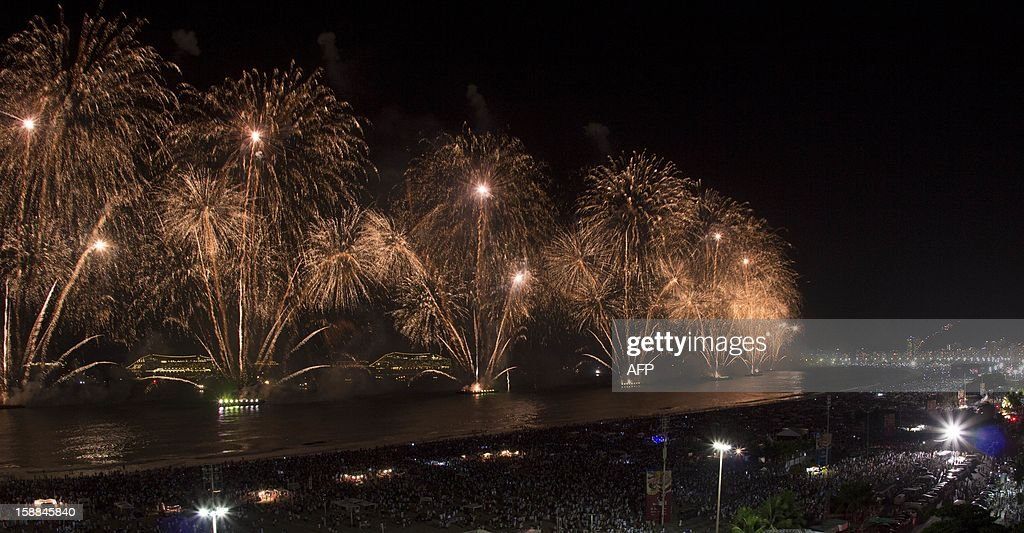 People watch fireworks along Copacabana Beach in Rio de Janeiro on January 1, 2013, during celebrations by over three million people attending New Year's Eve festivities. World cities from Sydney and Hong Kong to Dubai and London rang in the New Year with spectacular fireworks, as revelers at Times Square in New York sought to top off the global extravaganza. AFP PHOTO / ARI VERSIANI