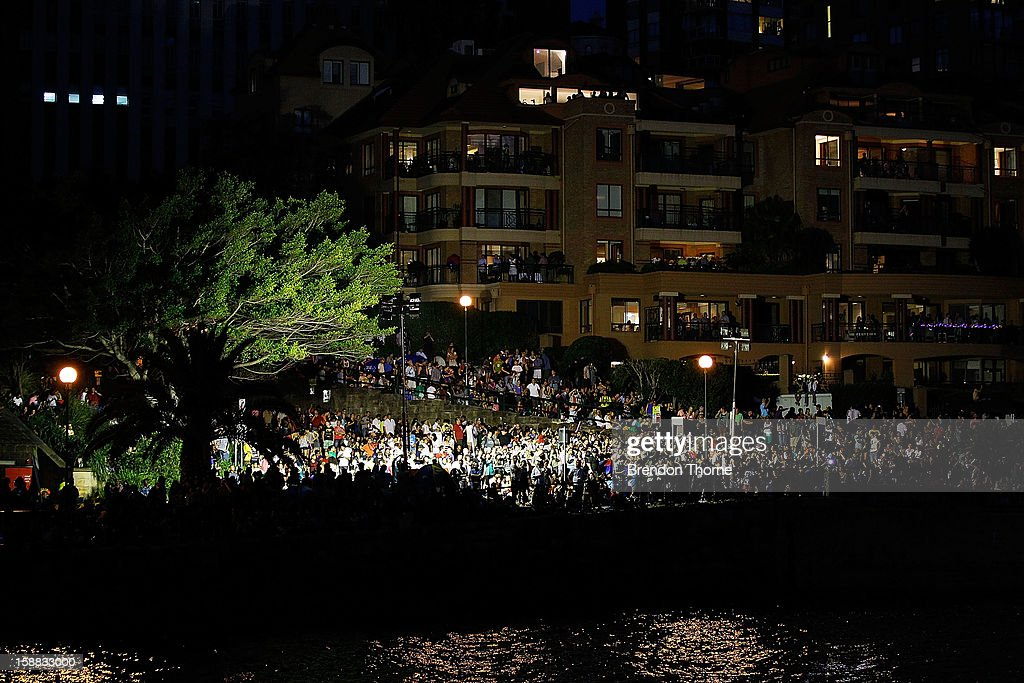 People watch fireworks around the harbour during New Years Eve celebrations on Sydney Harbour on December 31, 2012 in Sydney, Australia.