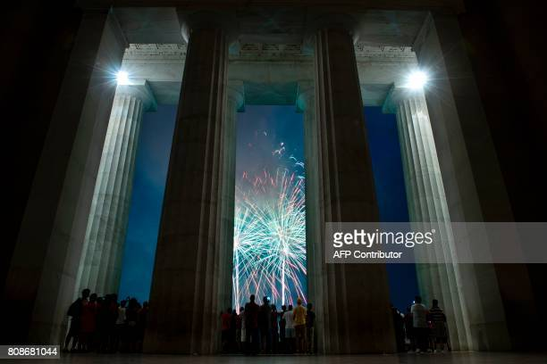 People watch fireworks as they celebrate US independence day on July 4 2017 in Washington DC / AFP PHOTO / Brendan Smialowski