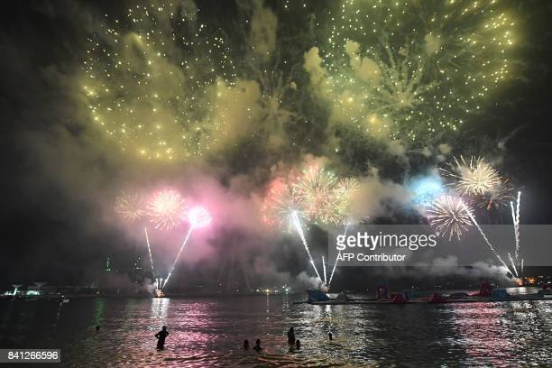 People watch fireworks in Dubai on August 31 2017 on the eve of the Muslim holiday of Eid alAdha the 'Feast of Sacrifice' which marks the end of the...