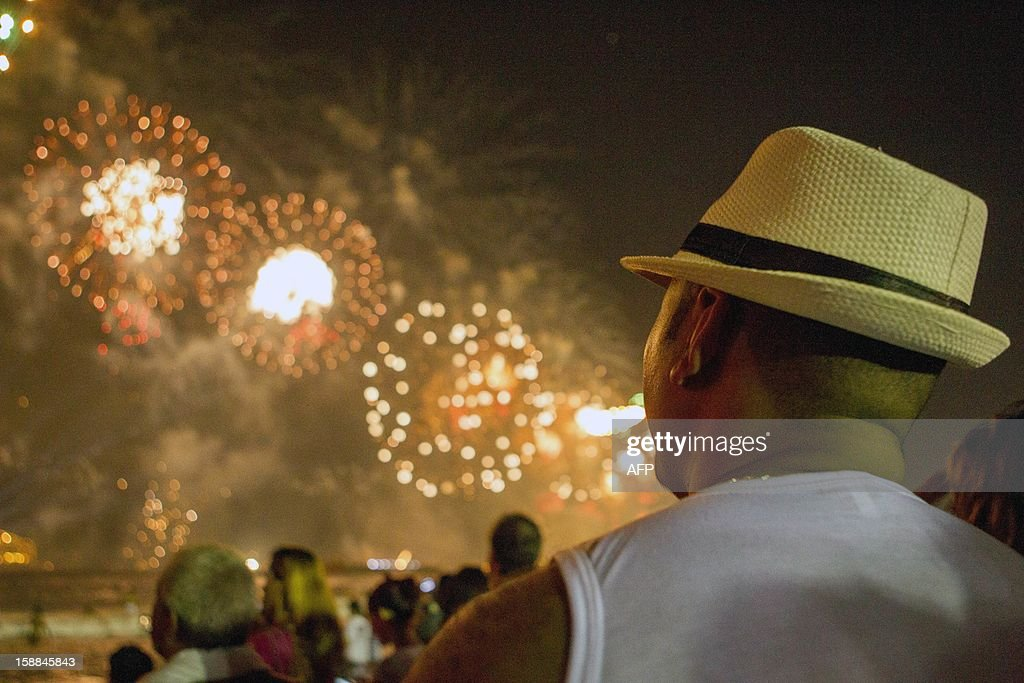 People watch fireworks light up the sky along Copacabana Beach in Rio de Janeiro on January 1, 2013, during celebrations by over three million people attending New Year's Eve festivities. World cities from Sydney and Hong Kong to Dubai and London rang in the New Year with spectacular fireworks, as revelers at Times Square in New York sought to top off the global extravaganza.