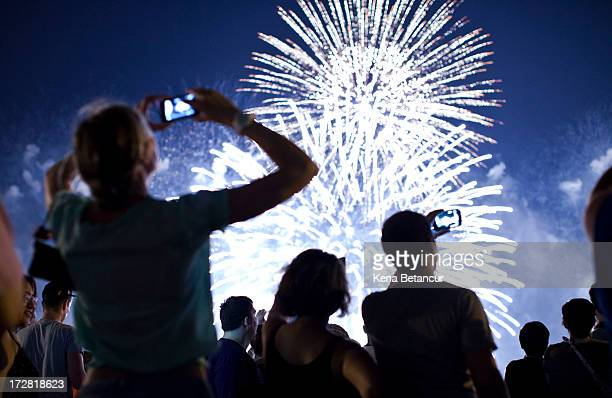 People watch fireworks light up the sky over New York City on July 4 2013 in Weehawken New Jersey July 4th is a national holiday with the nation...