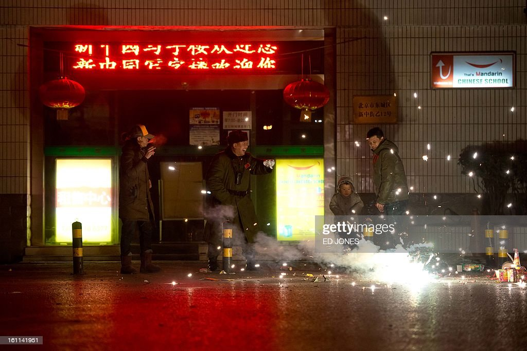 People watch fireworks on a street in Beijing on February 9, 2013. Revellers across the city lit fireworks as China welcomed the lunar new year of the snake. AFP PHOTO / Ed Jones