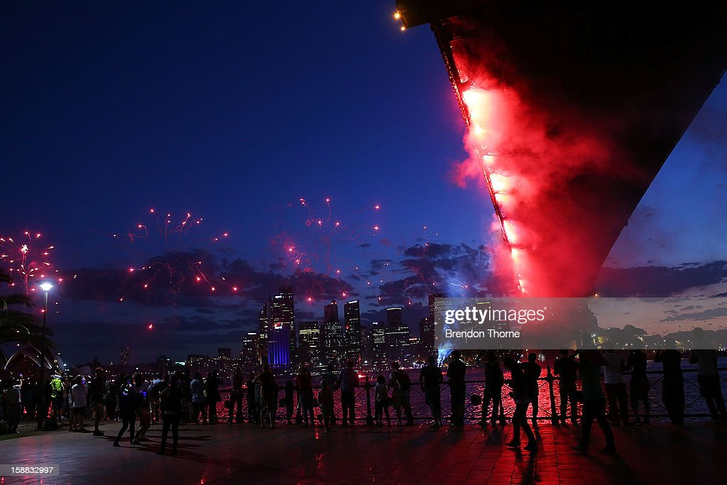 People watch fireworks under The Sydney Harbour Bridge during New Years Eve celebrations on Sydney Harbour on December 31, 2012 in Sydney, Australia.
