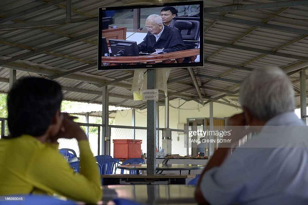 People watch former Cambodian Khmer Rouge leader 'Brother Number Two' Nuon Chea (top) on a livefeed video during the trial of former Khmer Rouge leaders at the Extraordinary Chamber in the Courts of Cambodia (ECCC) in Phnom Penh on October 31, 2013. Two former Khmer Rouge leaders make their closing statements on October 31 in the landmark trial against surviving members of the murderous regime at Cambodia's UN-backed war crimes court.