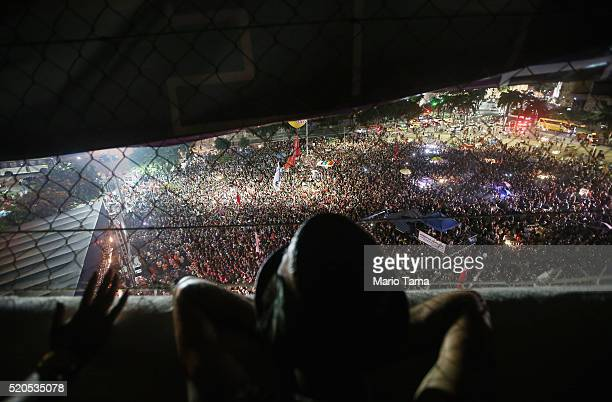 People watch former President Luiz Inacio Lula da Silva 'Lula' speak at a rally supporting President Dilma Rousseff in the historic Lapa neighborhood...
