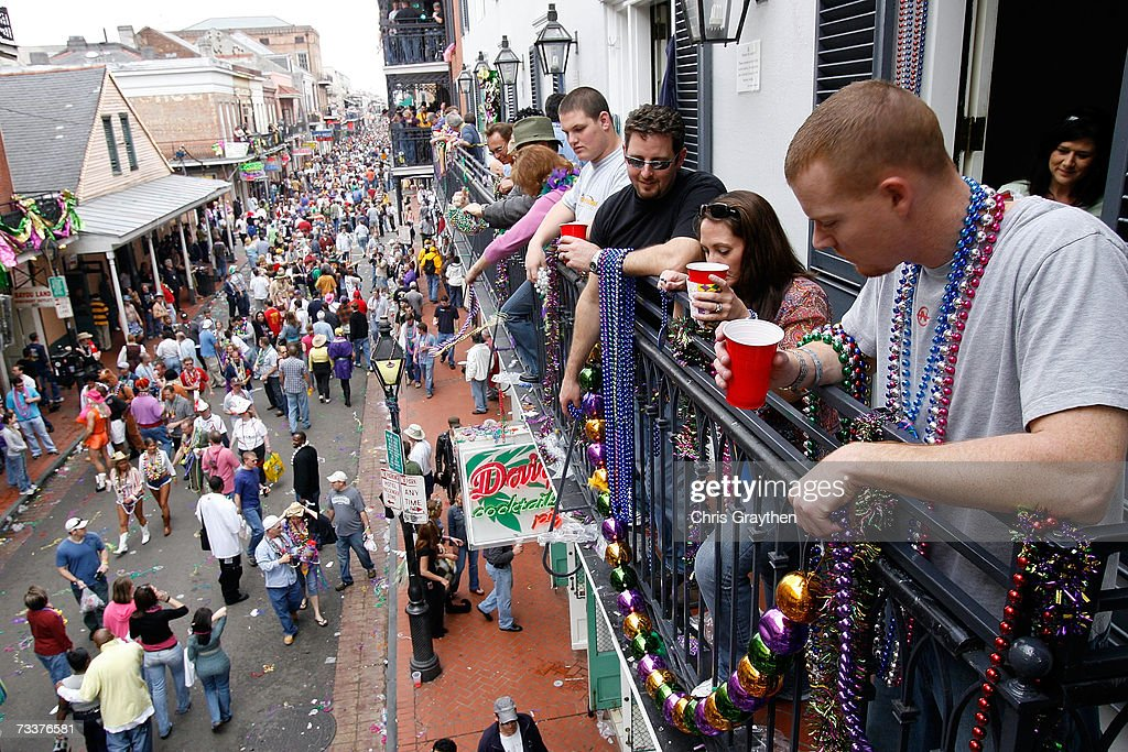 People watch from a balcony as revelers walk along Bourbon Street on Mardi Gras Day February 20 2007 in New Orleans Louisiana This is the second...