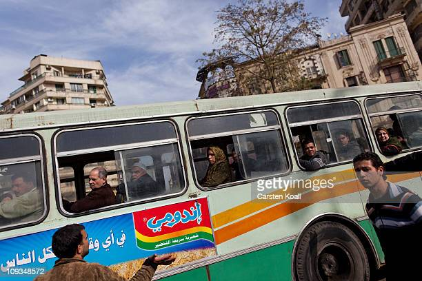 People watch from a bus as they pass a rally at Tharir Square Feburary 22 2011 in Cairo Egypt Many hundreds people attended rally in central Cairo's...