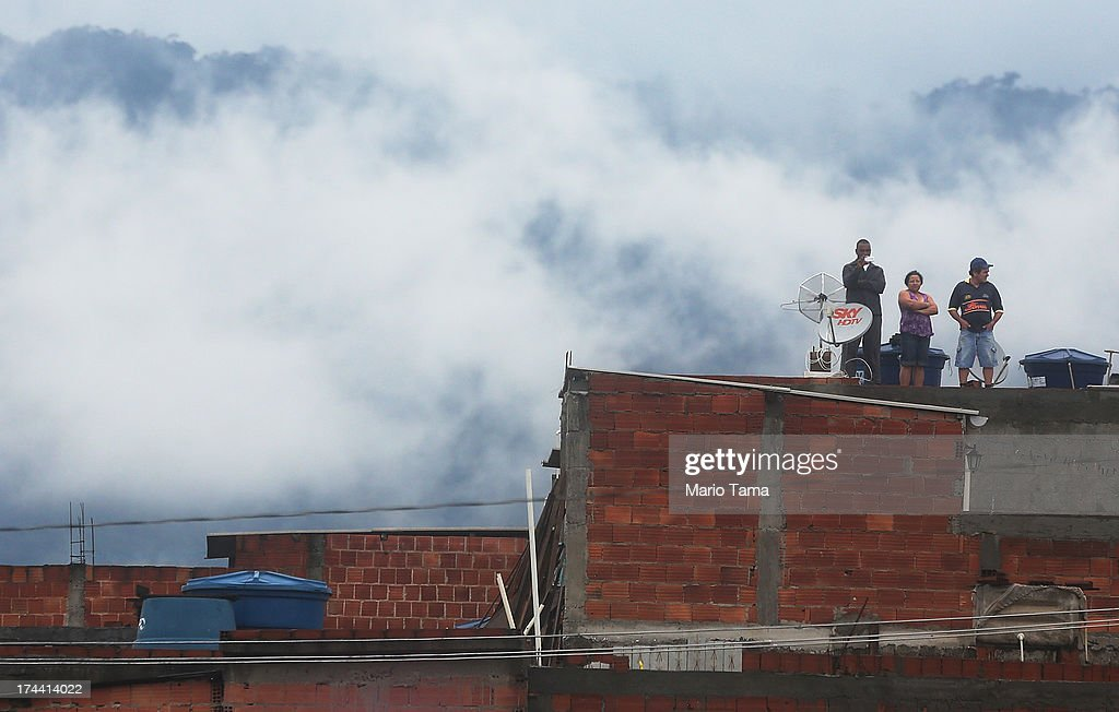 People watch from a rooftop as Pope Francis speaks in the Varghina favela, or shantytown, on July 25, 2013 in Rio de Janeiro, Brazil. More than 1.5 million pilgrims are expected to join Pope Francis for his visit to the Catholic Church's World Youth Day celebrations. Pope Francis will deliver his welcome address to the celebrations on Copacabana Beach later today as World Youth Day runs July 23-28.