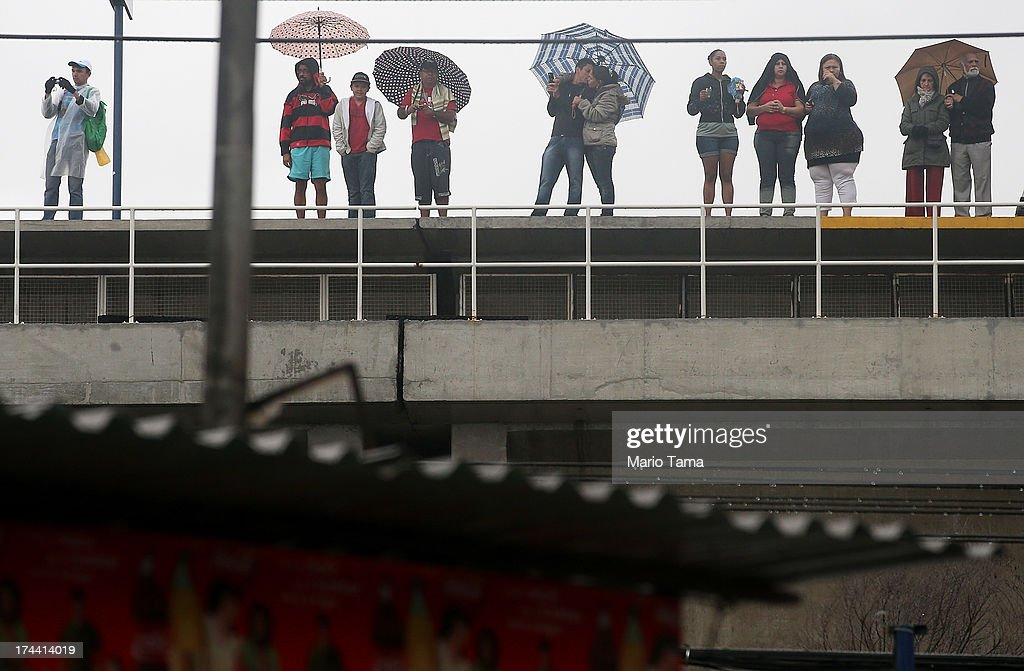 People watch from a train platform as they await the arrival of Pope Francis to tour the Varghina favela, or shantytown, on July 25, 2013 in Rio de Janeiro, Brazil. More than 1.5 million pilgrims are expected to join Pope Francis for his visit to the Catholic Church's World Youth Day celebrations. Pope Francis will deliver his welcome address to the celebrations on Copacabana Beach later today as World Youth Day runs July 23-28.