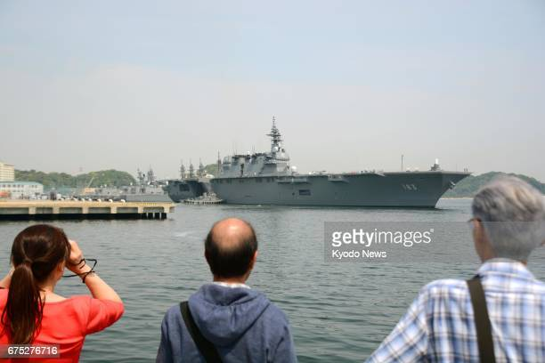 People watch from ashore as the Japanese Maritime SelfDefense Force helicopter carrier Izumo leaves Yokosuka base in Kanagawa Prefecture southwest of...