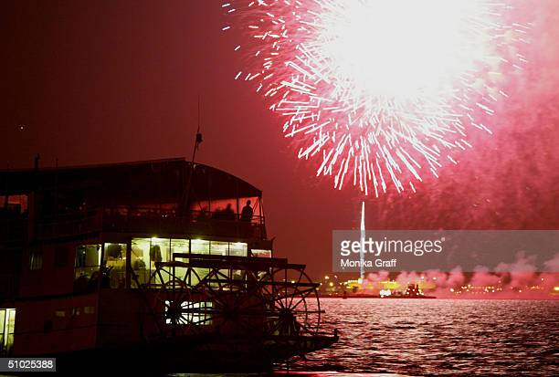 People watch from the deck of a paddle boat in the New York Harbor as fireworks illuminate the sky around the Statue of Liberty during the annual...