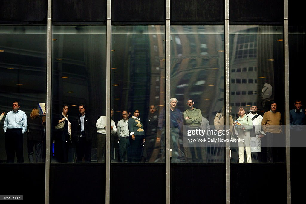 People watch from the nearby JP Morgan Chase offices as a large group of protesters organized by the Neighborhood Assistance Corporation of America...
