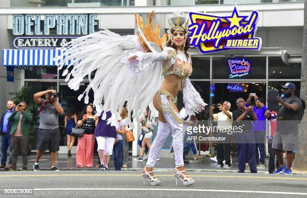 People watch from the sidewalk as Carnival dancers make their way down Hollywood Boulevard at the 6th annual Hollywood Carnival Parade celebrating...