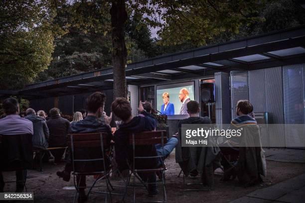 People watch German Chancellor and Christian Democrat Angela Merkel debate with her main opponent Social Democrat and chancellor candidate Martin...