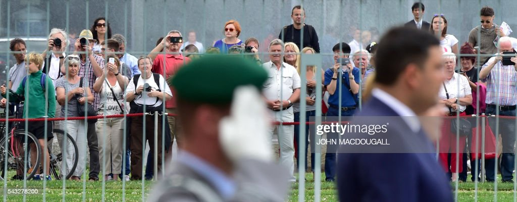 People watch German chancellor Angela Merkel (R) and Ukraininian Prime Minister Volodymyr Groysman listening to their national anthems during a welcoming ceremony before talks at the chancellery in Berlin on June 27, 2016. / AFP / John MACDOUGALL