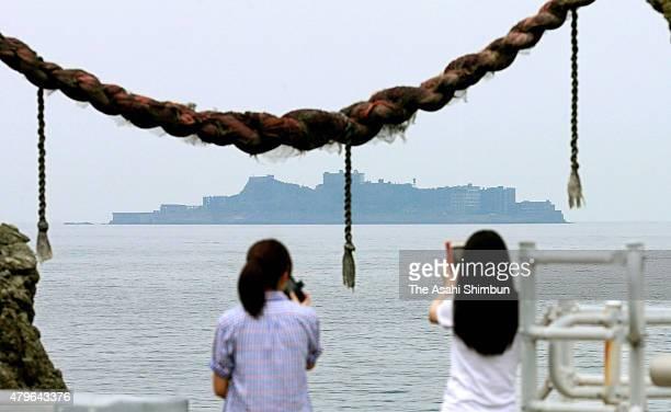 People watch Hashima Island aka Battleship Island ahead of the island's registration to the world heritage sites on July 5 2015 in Nagasaki Japan...