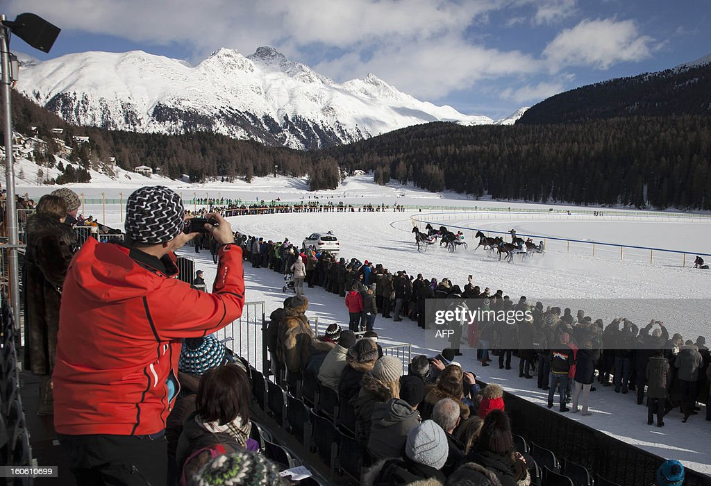 People watch jockeys competing in the White Turf horse racing event in St. Moritz on February 3, 2013. The races are held on the frozen lake of the Swiss mountain resort. HEGER
