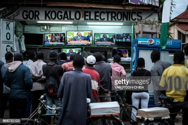 People watch live broadcast as Uhuru Kenyatta is declared the winner following presidential reelection results by Kenya's Independent Electoral and...