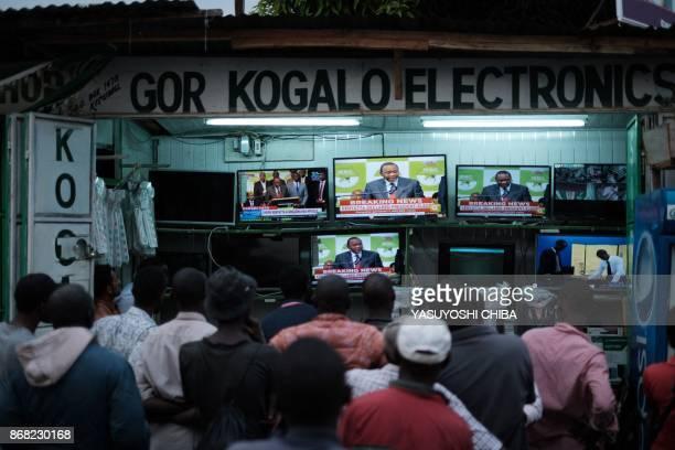TOPSHOT People watch live broadcast as Uhuru Kenyatta is declared the winner following presidential reelection results by Kenya's Independent...