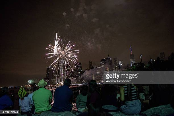 People watch Macy's Fourth of July Fireworks from Brooklyn Bridge Park on July 4 2015 in the Brooklyn borough of New York City The celebrations mark...