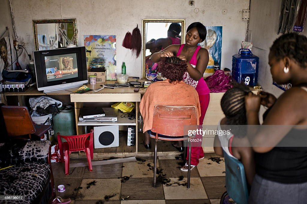 People watch Madiba's State Funeral at a salon on December 15, 2013 in Tokoza, South Africa. Nelson Mandela passed away on the evening of December 5, 2013 at his home. He is laid to rest at his homestead in Qunu during a State Funeral.