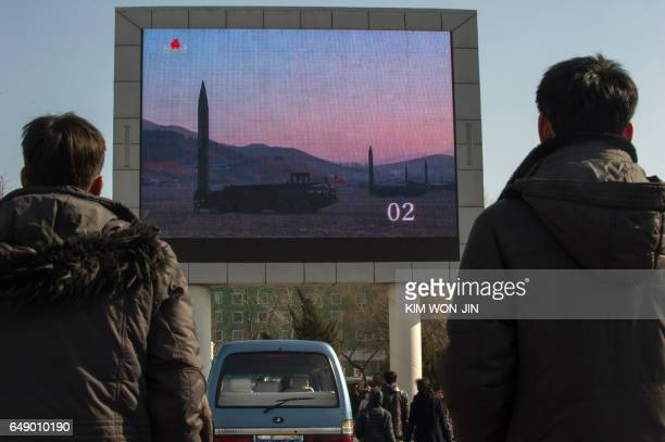 TOPSHOT People watch news footage of a missile launch on a giant television screen outside the main railway station in Pyongyang on March 7 2017...