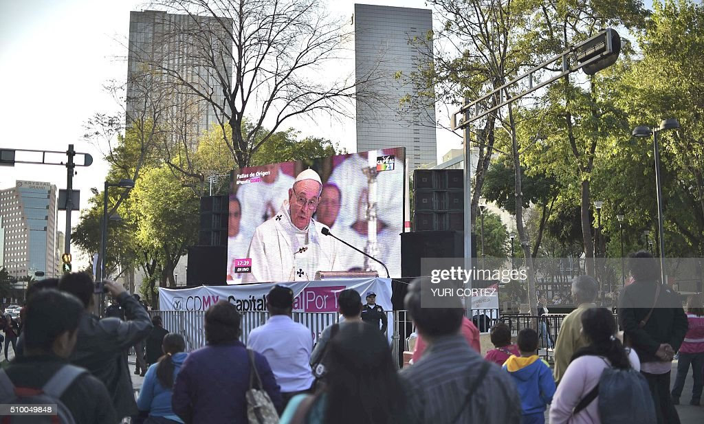 People watch on a large screen placed in Alameda Park the open-air mass officiated by Pope Francis in the Basilica of Our Lady of Guadalupe in Mexico City on February 13, 2016. Pope Francis urged Mexico's leaders Saturday to provide 'true justice' to citizens hit by drug violence and called on bishops to courageously fight the scourge plaguing the country. AFP PHOTO/ Yuri CORTEZ / AFP / YURI CORTEZ