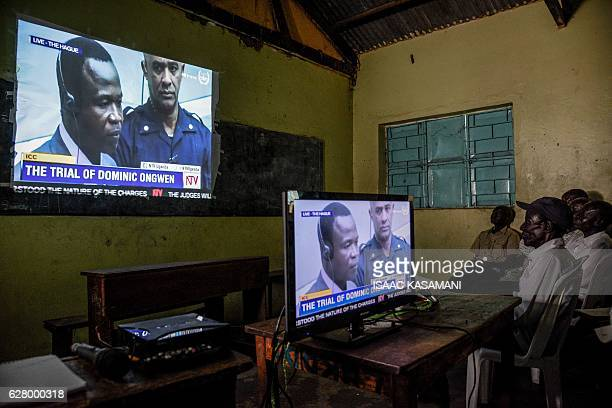 TOPSHOT People watch on tv the screening of the start of the ICC trial of former child soldierturnedwarlord Dominic Ongwen in Lukodi Uganda on...