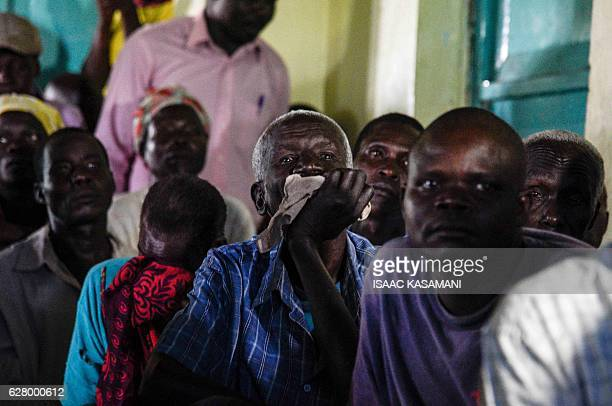 People watch on tv the screening of the start of the ICC trial of former child soldierturnedwarlord Dominic Ongwen in Lukodi Uganda on December 6...