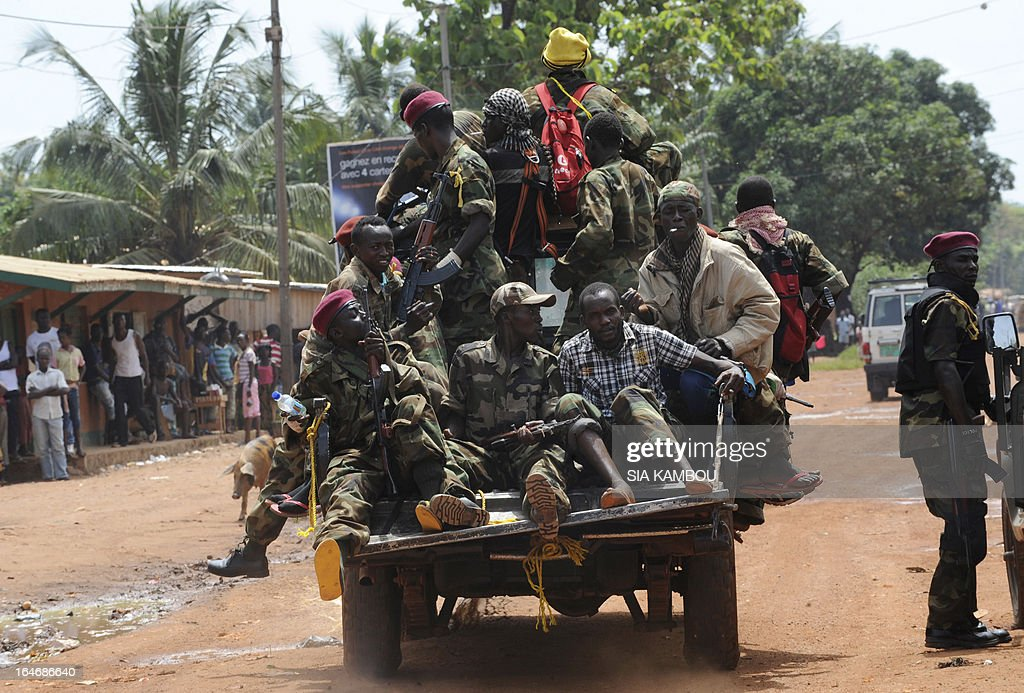 People watch rebels of the Seleka coalition in their car as they search for people suspected of looting in a neighbourood of Bangui on March 26, 2013. Central African Republic strongman Michel Djotodia was set to unveil a new government on March 26 after declaring he would rule by decree following the latest coup in the notoriously unstable nation. Looters were on the rampage in the capital Bangui after Djotodia's Seleka rebel coalition seized control in a rapid-fire weekend assault that forced president Francois Bozize into exile and was condemned by the international community.