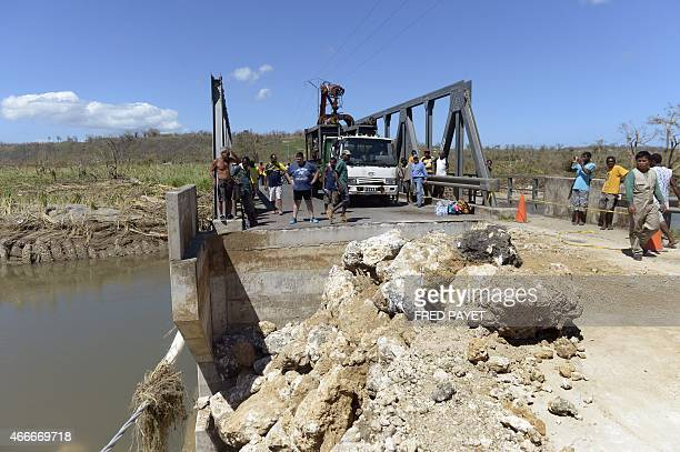 People watch repair work on the Teouma bridge on March 17 2015 near Port Villa after Severe Tropical Cyclone Pam hit the Pacific nation of Vanuatu on...