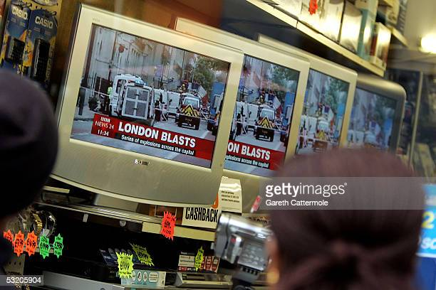 People watch reports on televisions in a shop near Edgware Road station following a series of explosions which ripped through London's underground...