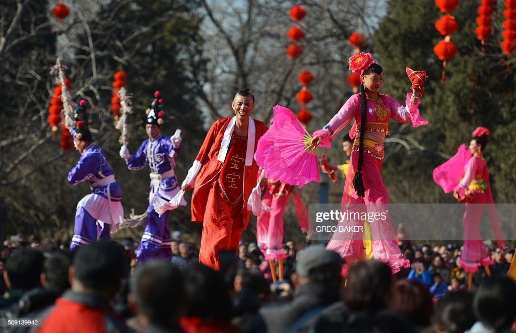 People watch stilt dancers in a park in Beijing during Lunar New Year celebrations on February 9, 2016. Millions of Chinese are celebrating Spring Festival, the most important holiday on the Chinese calendar, which this year marks the beginning of the Year of the Monkey. AFP PHOTO / GREG BAKER / AFP / GREG BAKER