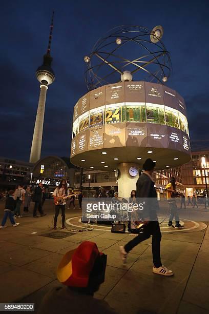 People watch street musicians peform under the Urania world time zone clock at Alexanderplatz on a warm summer evening on July 13 2016 in Berlin...