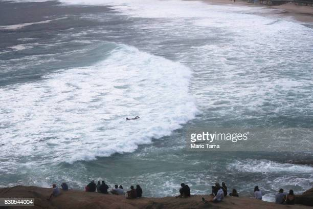 People watch surfers on Arpoador rock during strong winter swells on the Atlantic Ocean on August 11 2017 in Rio de Janeiro Brazil Waves were...