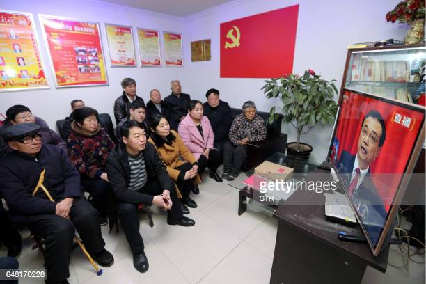 People watch television coverage of China's Premier Li Keqiang reading his report during the National People's Congress opening ceremony at a...