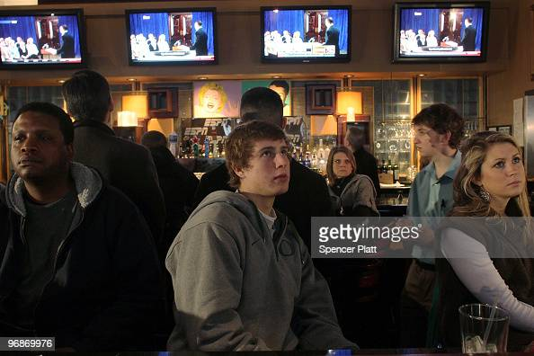 People watch television monitors as professional golfer Tiger Woods makes his first public statement concerning a string of infidelities he has...