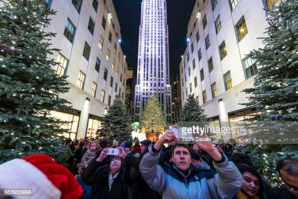 People watch the 2016 Saks Fifth Avenue Holiday Light Show and take photo from Rockefeller Center. Christmas tree stands at front of Rockefeller Center and illuminates.