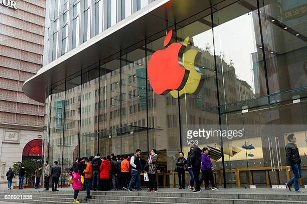 People watch the Apple flagship store which lights up the red logo in the World AIDS Day 2016 to raise awareness for the AIDS pandemic at Huangpu...